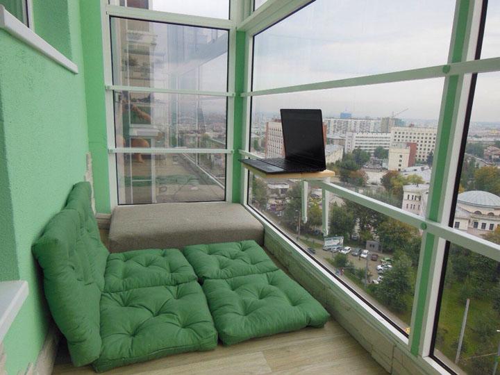 Зеленые подушки вместо кровати на панорамном балконе