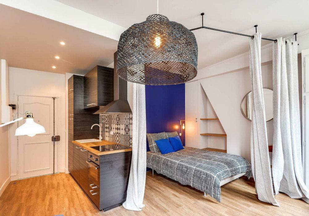 Зонирование квартиры-студии шторами на потолочном карнизе
