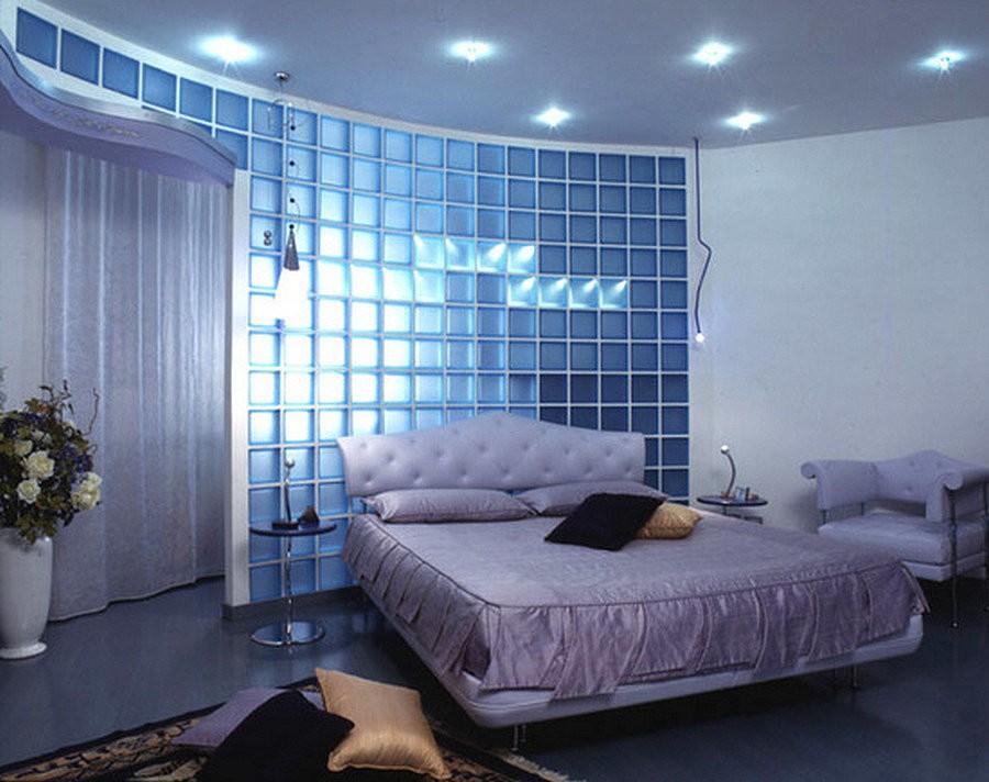 Широкая кровать в спальне с перегородкой из стеклянных блоков