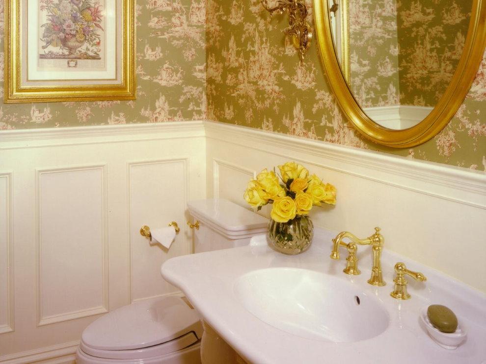 Позолоченные краны на фарфоровой раковине в ванной с обоями