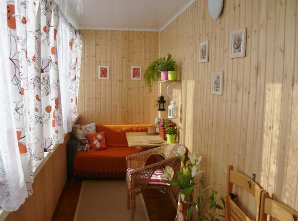 Светлые шторы на балконе с диваном