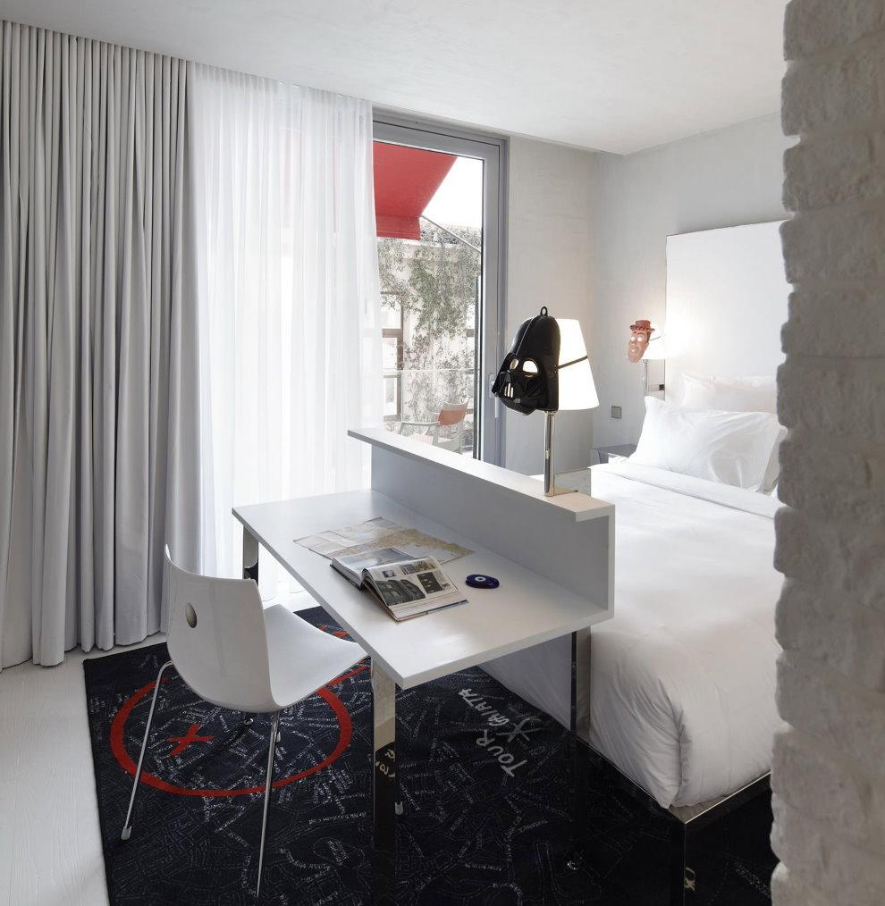 Небольшой столик около кровати в маленькой спальне