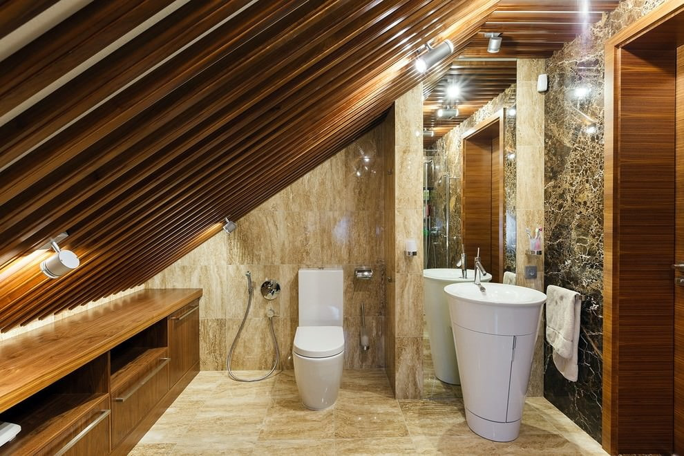 Белый унитаз на полу ванной в мансарде