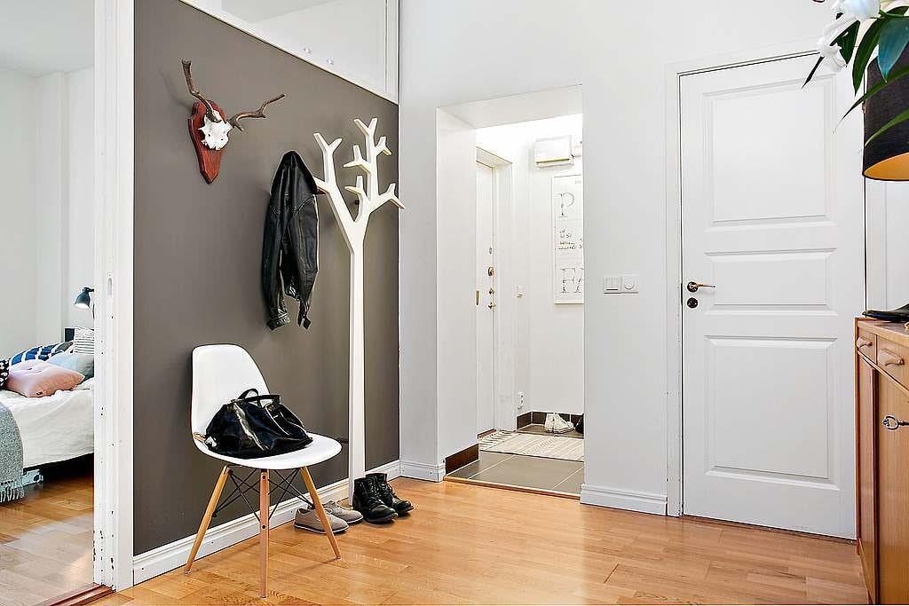 Белая вешалка в прихожей на фоне серой стены