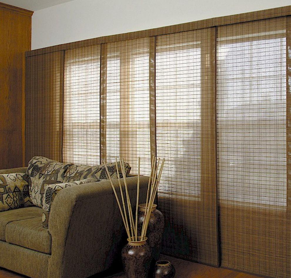 Раздвижные шторы из бамбука на окне гостиной за диваном