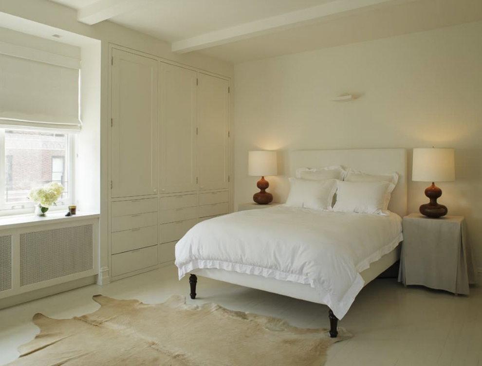 Белая кровать в спальне со светлыми стенами