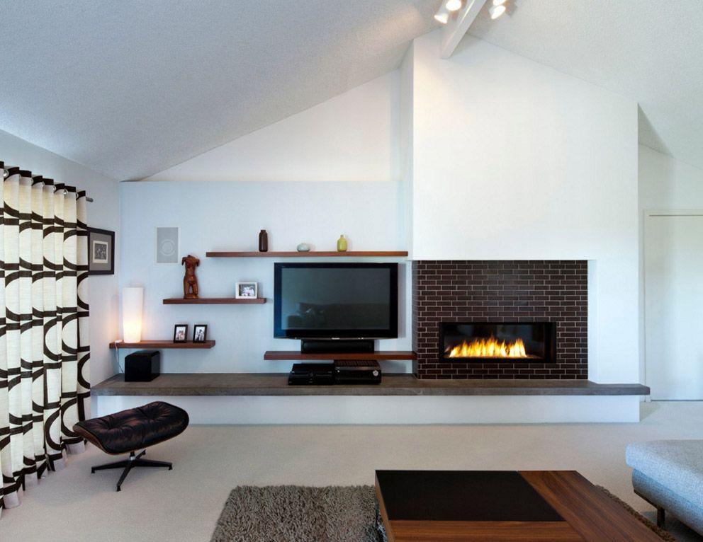 Белая стена гостиной с камином и телевизором