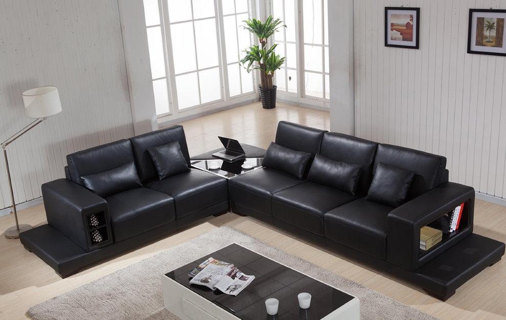 Черный угловой диван на ламинированном полу зала