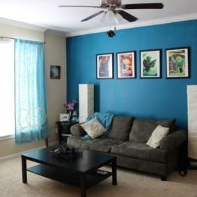 Серый диван вдоль синей стены