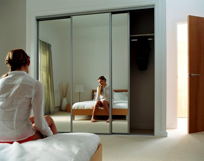 Отражение девушки в зеркальном шкафу в спальной комнате
