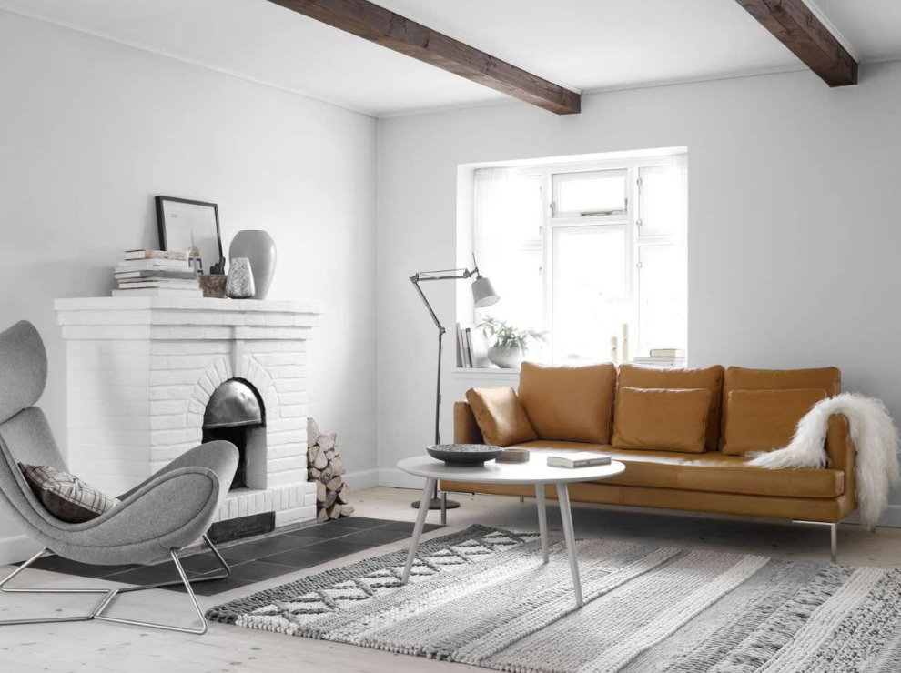 Кожаный диван в белой гостиной с камином