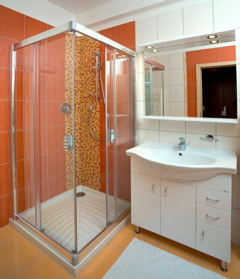 Белая раковина в ванной с душевой кабинкой
