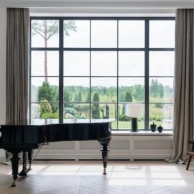 Черный рояль перед большим окном