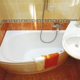 Оранжевое полотенце на бортике ванной