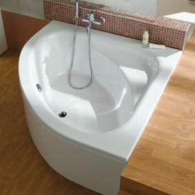 Белая чаша ванны на деревянном полу