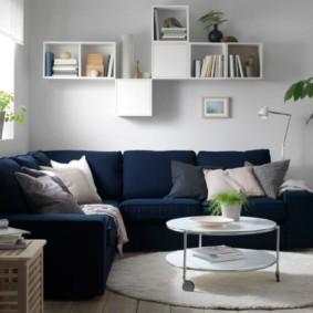 Полки с книгами над синим диваном