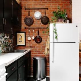 Сковородки на кирпичной стене кухни
