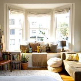 Подушки и игрушки в эркере гостиной квартиры