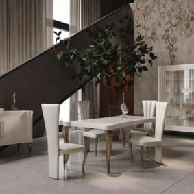 Обеденный стол в гостиной с лестницей