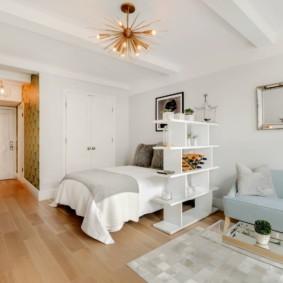 Белый стеллаж около кровати в квартире