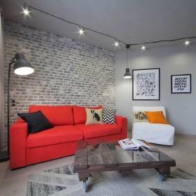 Красный диван в комнате небольшой площади