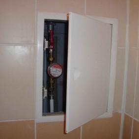 Водомер за приоткрытой дверкой сантехнического люка