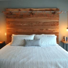 Лампочки на красных шнурах над деревянной кроватью