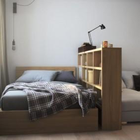 Низкий стеллаж между кроватью и диваном