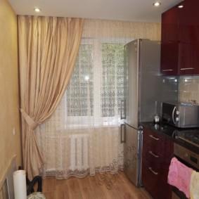 Холодильник возле окна с асимметричной шторой