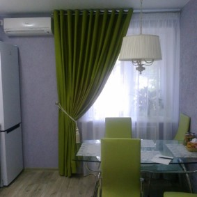 Зеленая штора на окне кухни в панельном доме