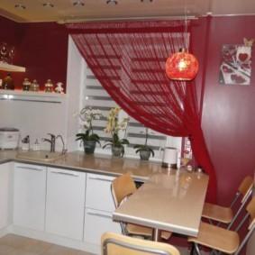 Красная штора на окне кухни с белой мебелью
