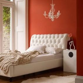 Белая кровать перед окном спальни