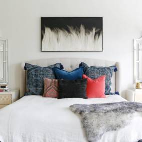 Разноцветные подушки на высокой кровати