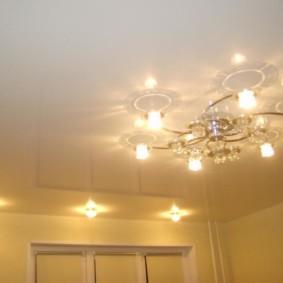 Комбинация точечных светильников с люстрой в зале
