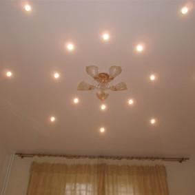 Точечные светильники вокруг люстры на потолке зала