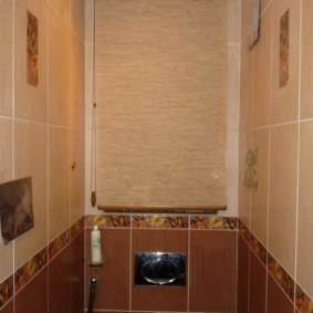 Открытая рулонная штора на стене за унитазом