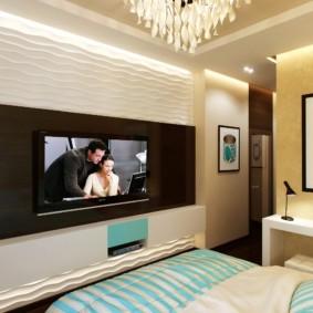 Интерьер небольшой спальни с телевизором на стене