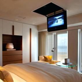 Телевизор на откидном люке в потолке спальни