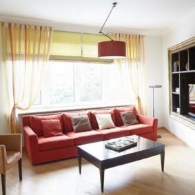 Красный диван перед окном в гостиной
