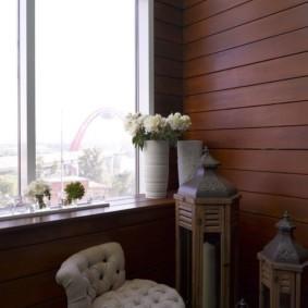 Ваза с живыми цветами на подоконнике балкона