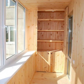 Шкаф с деревянными полками на лоджии двухкомнатной квартиры