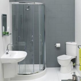 Белая сантехника в ванной с серой стеной