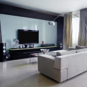 Прямой диван посередине просторной гостиной