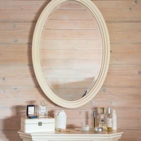 Овальное зеркало на стене из бруса