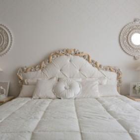 Белая кровать и маленькие зеркала