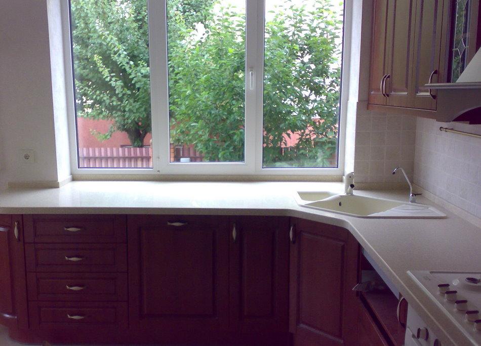 Трапециевидная мойка перед окном кухни в частном доме