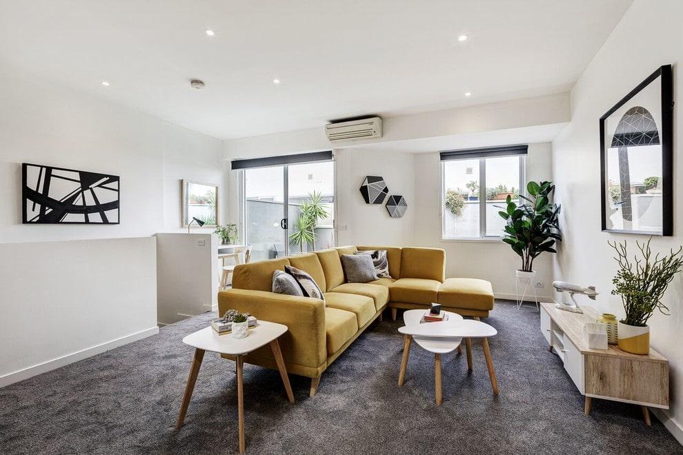 Горчичный диван в комнате с белыми стенами