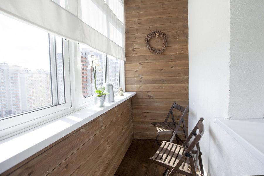Складные стульчики на лоджии с деревянной обшивкой