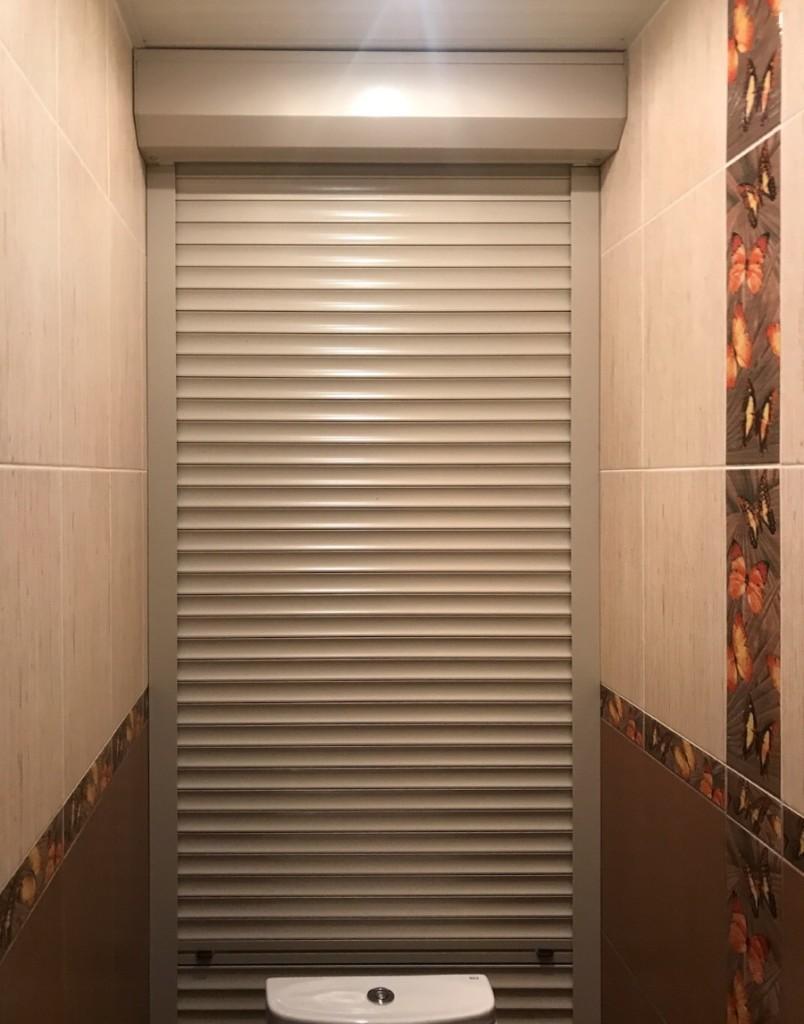 Узкий туалет с жалюзи на задней стенке