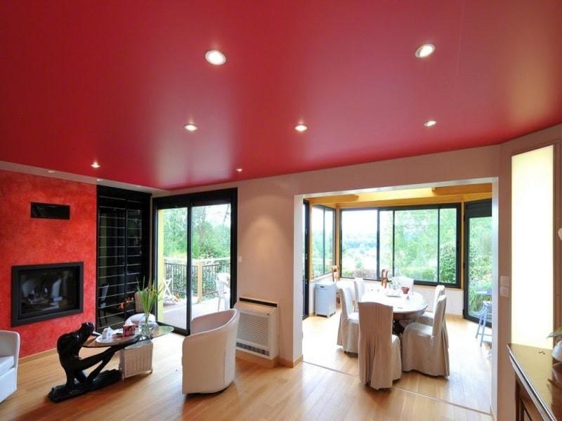Красный потолок в интерьере гостиной